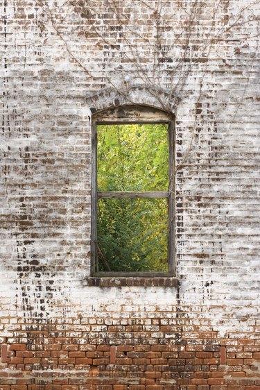 Window frame in decaying brick wall