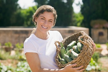 Woman holding a basket of courgettes