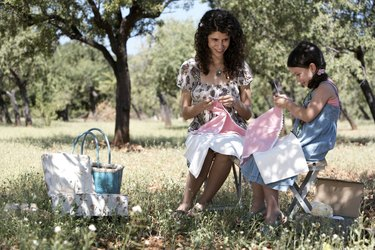 mother and daughter sewing in an orchard