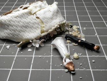 Bride and groom figurines lying at destroyed wedding cake on tiled floor
