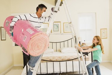 Man and daughter with bundle of insulation