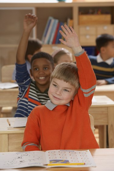 Close-up of a boy raising his hand in a classroom