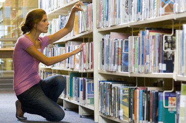 Woman selecting book from book shelf
