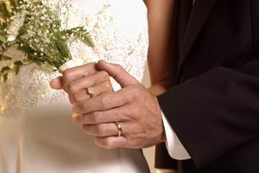 Hands with wedding rings and bouquet