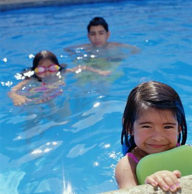 Boy (12-14) and two girls (4-7) swimming in pool (selective focus)