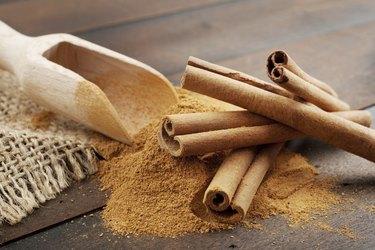 Cinnamon sticks and powder in wooden scoop