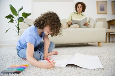 Daughter coloring with mother reading