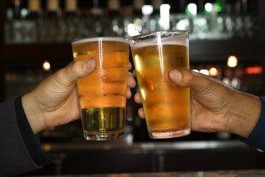 Hands of men toasting with beer