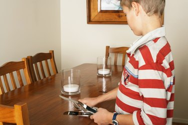 Boy (10-12) laying table with cutlery, side view