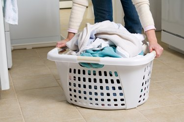 Cropped shot of woman picking up basket of laundry