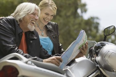 Couple standing by motorcycle and looking at map