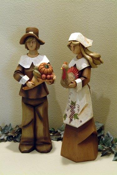 Two decorative wooden figurines of pilgrim couple