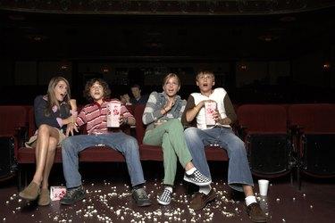 Four teenagers sitting in movie theatre auditorium