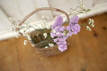 Vase of flowers in basket on wooden floor