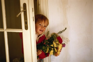 Boy (4-5) with bunch of flowers at door, smiling
