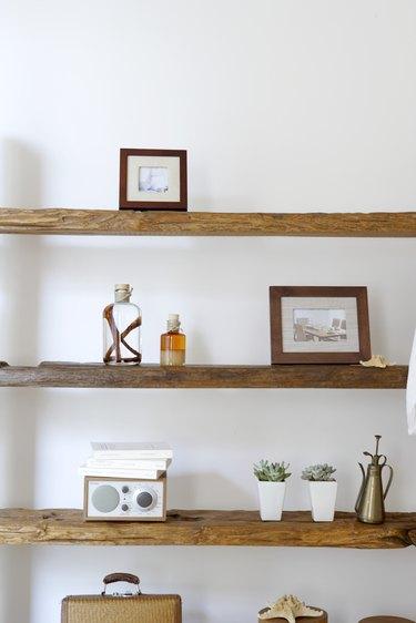 Framed photographs, decorative jars and potted plants on natural wooden shelves
