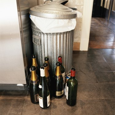 Empty champagne bottles by dustbin, elevated view