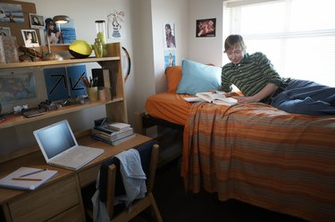 Young man reading on bed in dorm room, smiling, side view