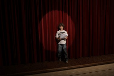 Spotlight on boy (10-12)  standing on stage, reading lines