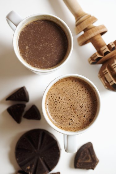 Two cups of abuelita hot chocolate with chocolate pieces, close-up