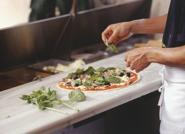 Man making pizza on table in kitchen, mid section, elevated view