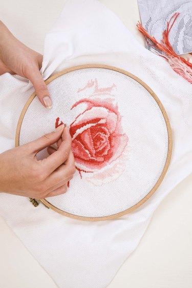 Woman cross stitching rose