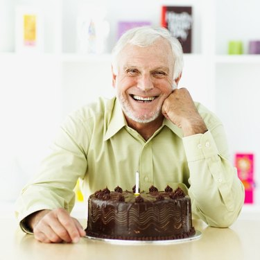 portrait of a senior man smiling in front of a birthday cake