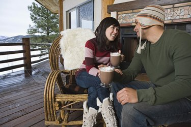 Couple drinking hot cocoa on deck