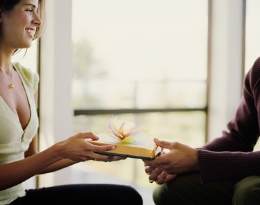 Man giving young woman gift, woman smiling, side view