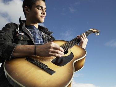 Teenage boy (15-17) playing guitar, low angle view