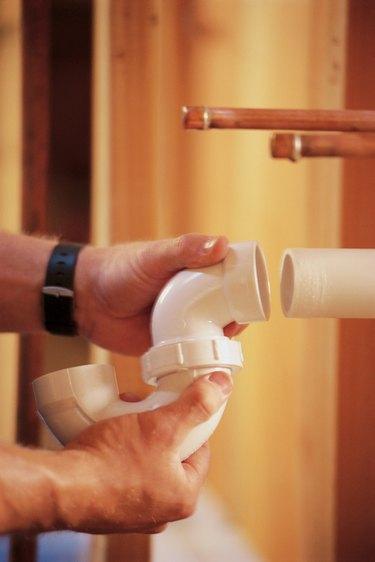 Plumber installing pipe