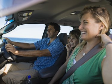 Smiling family riding in minivan