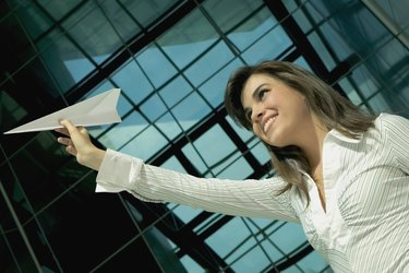 Low angle view of a young woman holding up a paper airplane