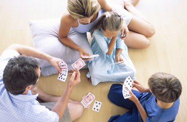 High angle view of family playing cards on floor