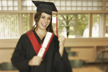 Excited teenage girl wearing cap and gown holding diploma