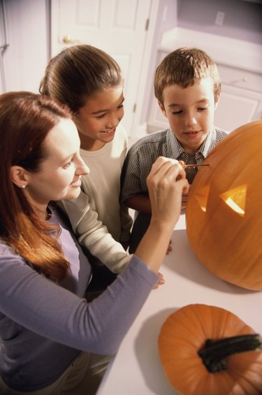 Mother carving a pumpkin with her son and daughter