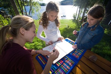 Mother and daughters drawing outdoors