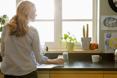 Woman looking out sunny window in kitchen