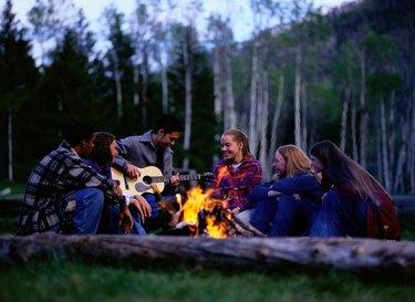 Teen Friends Singing Around Campfire