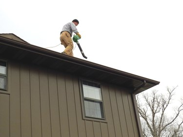Homeowner Cleaning Eaves Using a Leaf Blower