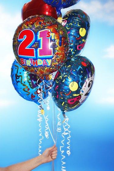 Woman holding twenty first birthday balloons