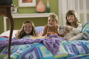 Girls playing video games at slumber party