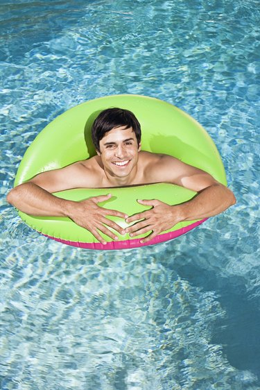Man in swimming pool with flotation device