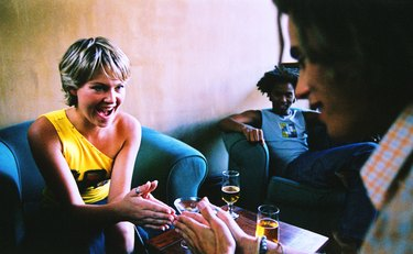 close-up of a group of friends talking over drinks in a living room