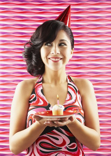 Native American woman holding birthday cupcake