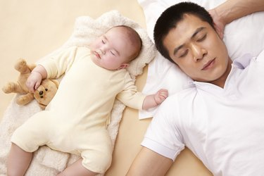 Father and baby (3-6 months) sleeping side-by-side
