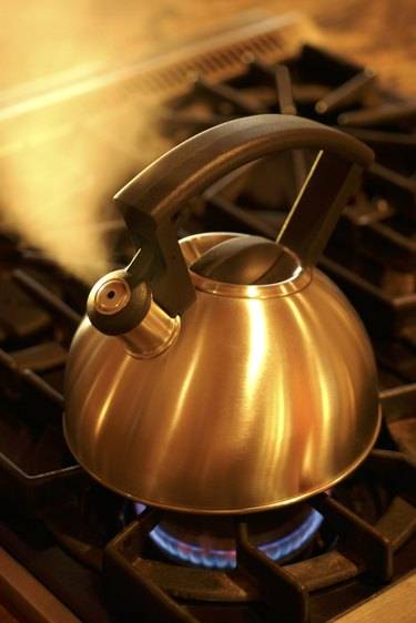 A stainless steel kettle blows steam while sitting on a hot burner of a stove.