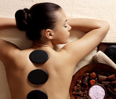 woman having stone massage in spa salon