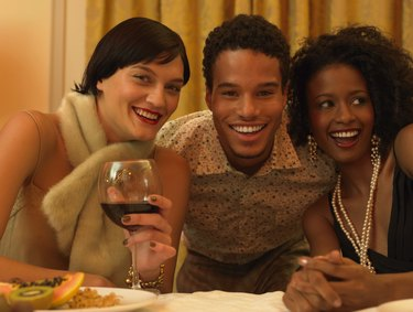 Portrait of a Man Sitting With Two Women in Evening Wear at a Dining Table, Smiling at the Camera