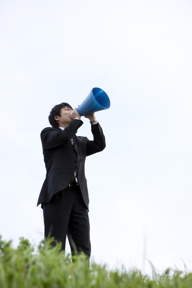 Businessman standing on grass with megaphone